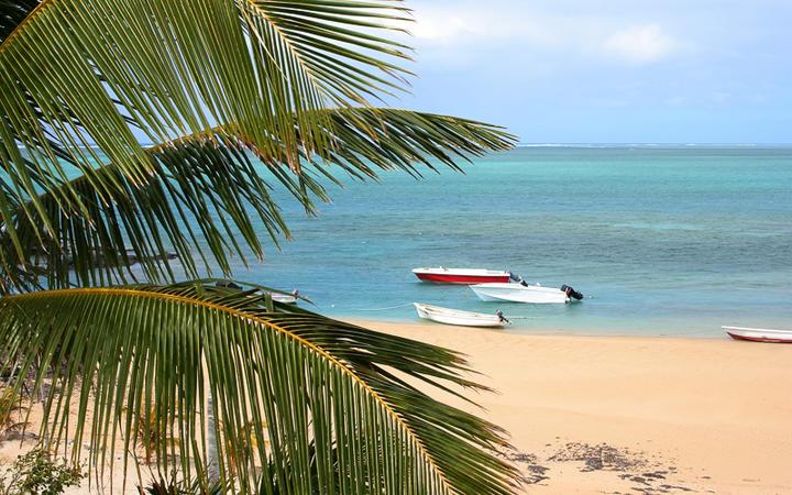 Goldener Strand mit Palmen und kleinen bunten Booten © Sapsiwai / Shutterstock.com