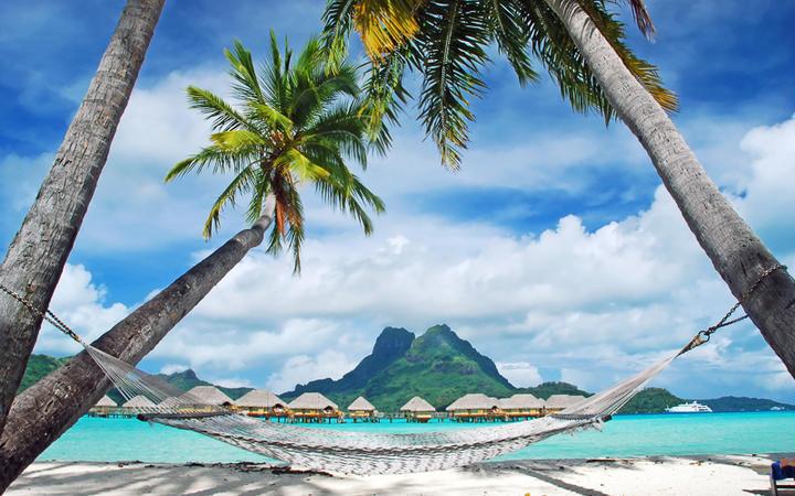 Palmen, Hängematte und Wasserbungalows auf der Trauminsel Bora Bora, Südsee © wilar / Shutterstock.com