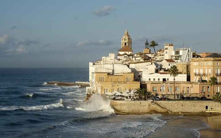 Ein stürmischer Tag in Sitges: die Kirche des heiligen Bartholomäus überragt die Stadt © BarracudaDesigns / Shutterstock.com