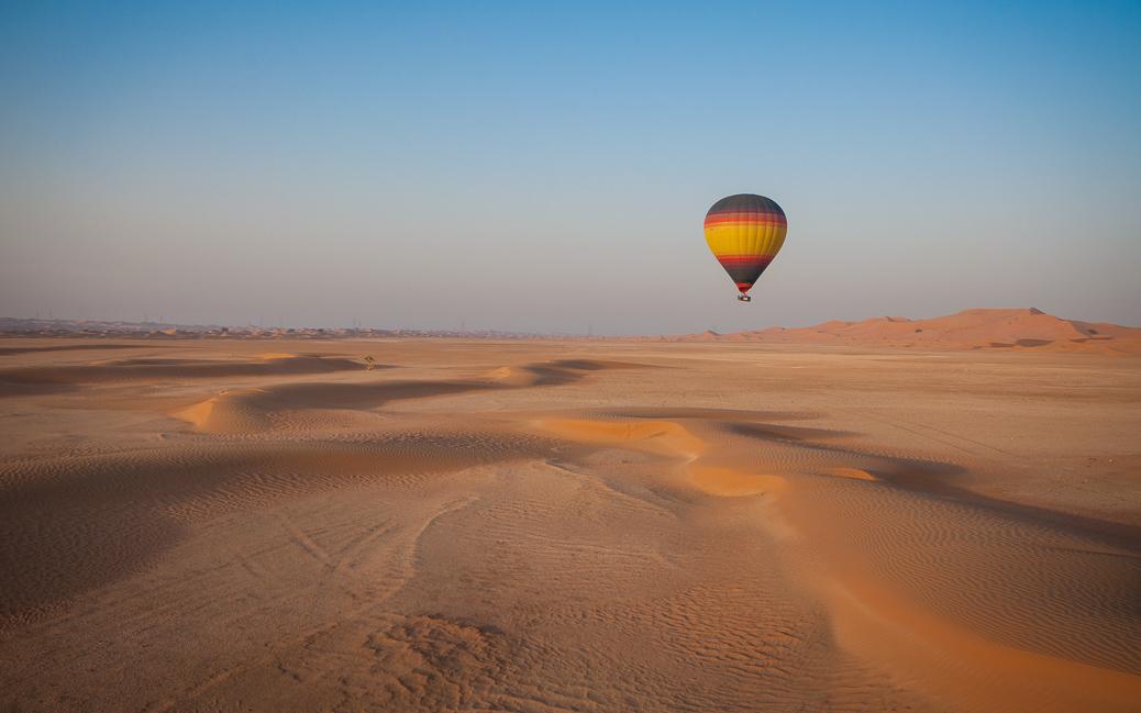 Hot Air Balloon floating over the desert sand © Joseph Borg / Shutterstock.com